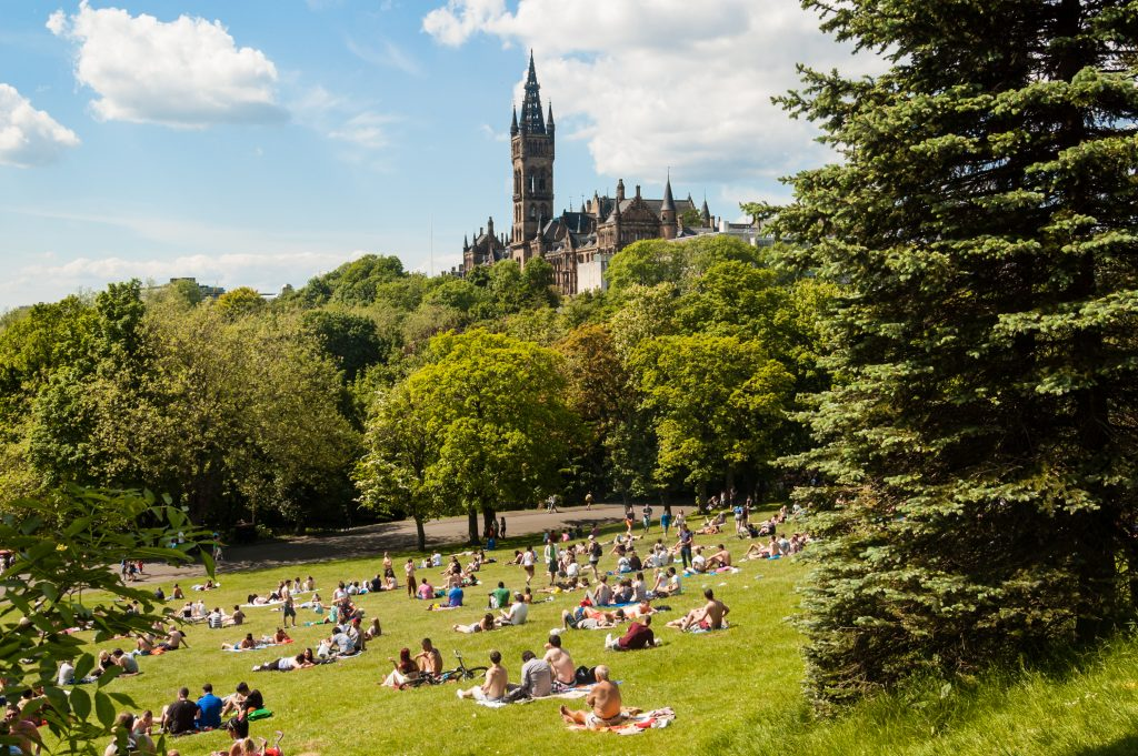 View of Kelvingrove Park full of people enjoying the Scottish summer with the main building of Glasgow University on the top of the hill.